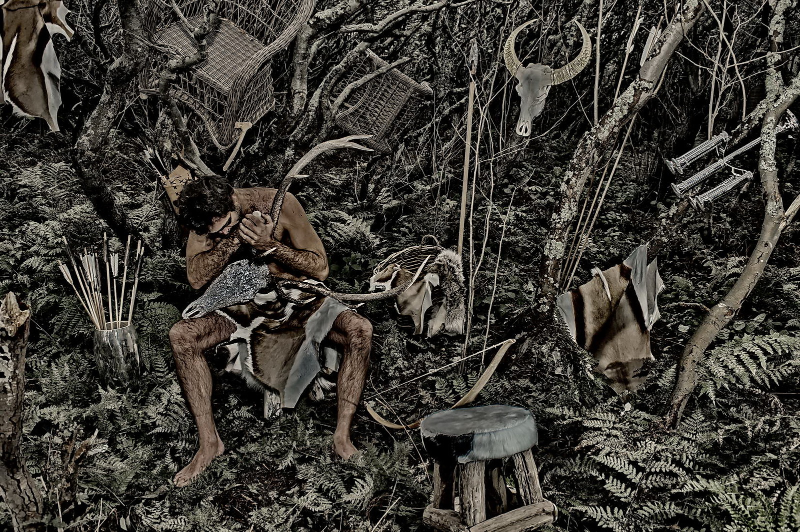 Ein nachkter Man in sylter Wald, nur mit einem Fell bestückt arbeitet und schnitzt einen Swarowski-Geweih. Drumherum sind diverse Gegenstände verteilt