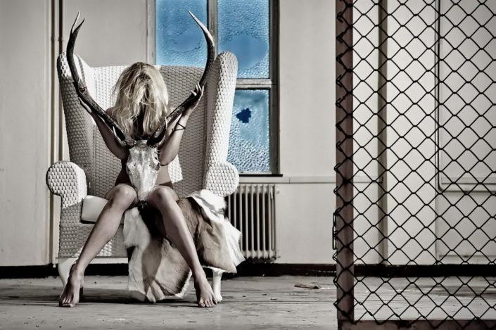 Eine nackte Frau sitzt auf einem weissem Sessel mit höher Lehne, in der Hand hält sie ein Geweih mitSwarowski-Steinen bestückt. Der raum ist alt und staubig
