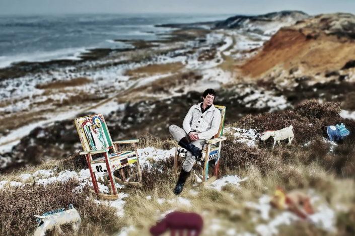 Ein trauriger Man sitzt in morsumer Landschaf auf Sylt in einem Stuhl, um ihn sind Plyschtiere verteilt