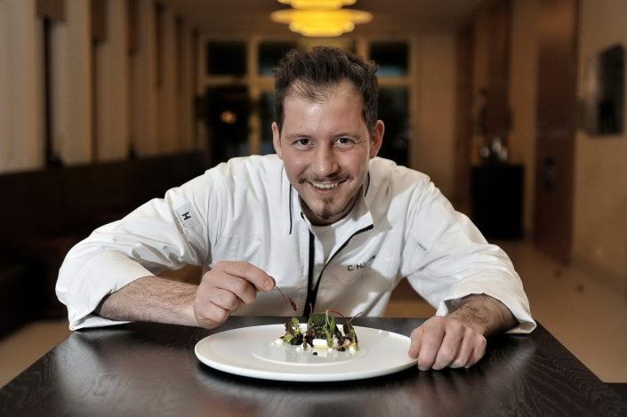 Das Bild zeigt den Pattisier Christioan Hümbs wie er gerade ein von seinen essen vorbereitet.