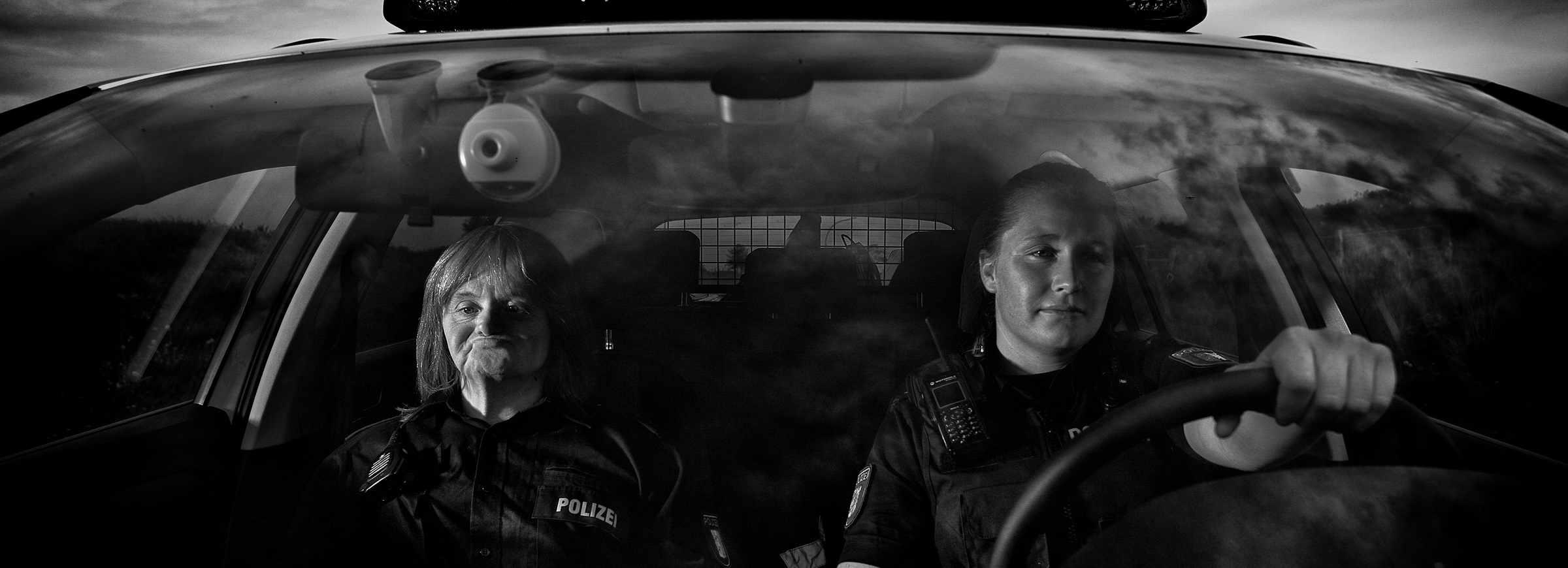 """Ein junge Polizistin sitzt am Steuer des Polizeiwagen, neben ihr sitzt der """"Kommisar"""""""
