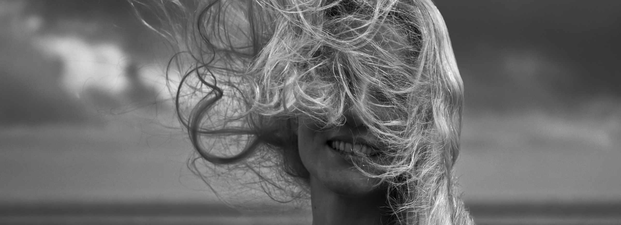 Ein Porträt von einer Frau deren Haare sind voll von Wind verweht