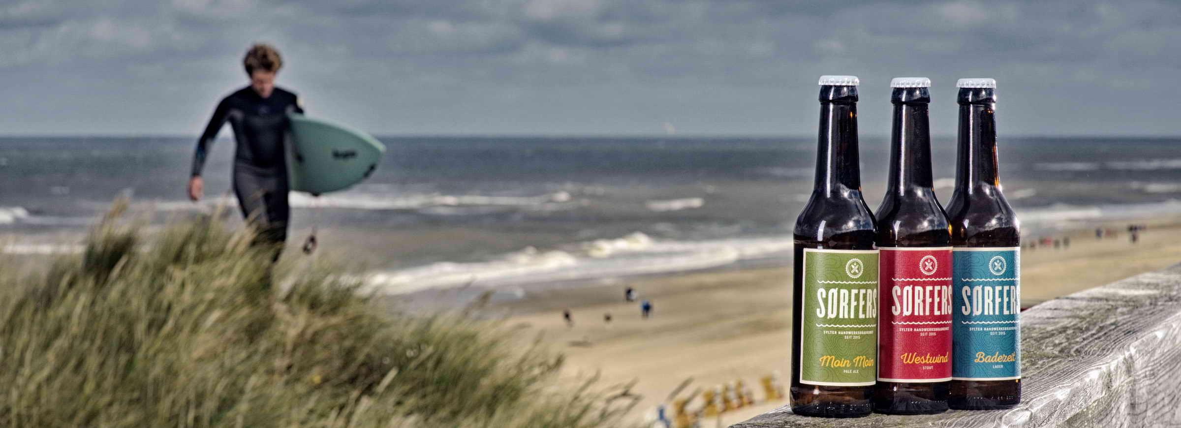 In Vordergrund auf dem Holzsteg-Gelände am Strand in Wenningstedt auf Sylt stehen drei Flaschen von SORFERS-Bier, in Hintergrund ist ein Surfer der gerade auf den Betrachter zu geht